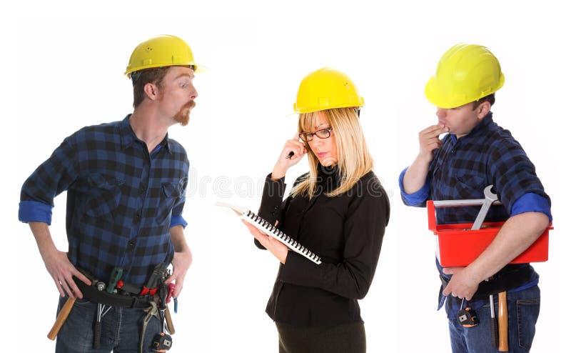 Mulher de negócios e trabalhadores da construção irritados fotos de stock