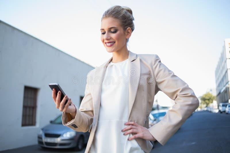 Mulher de negócios elegante de sorriso que olha seu smartphone foto de stock