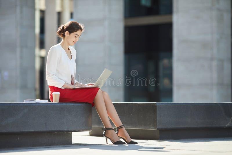 Mulher de negócios elegante Using Laptop Outdoors fotografia de stock