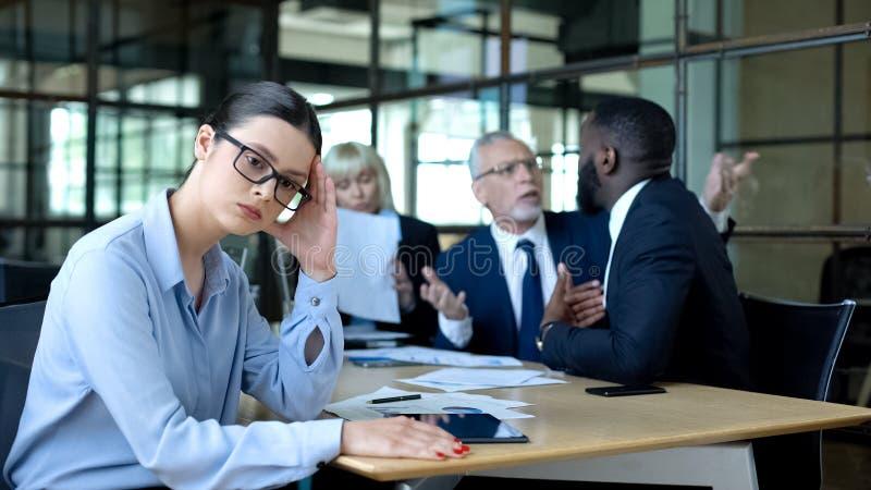 Mulher de negócios em estresse que sofre uma atmosfera de escritório tensa, colegas gritando imagens de stock