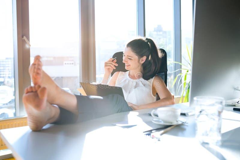 Mulher de negócios em seu escritório que senta-se com pés na mesa imagens de stock