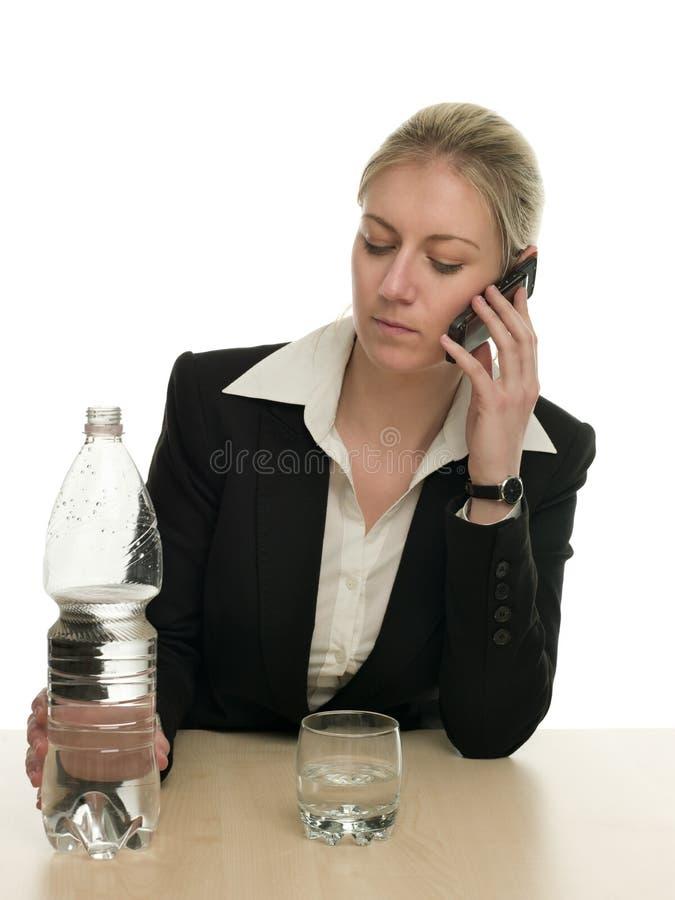 Mulher de negócios em um telefone pronto para derramar a água foto de stock royalty free