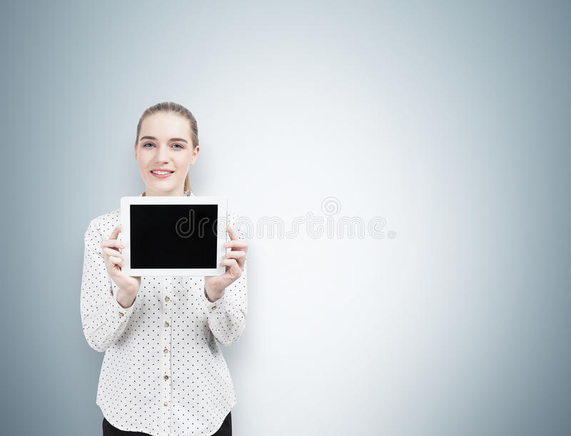 Mulher de negócios em uma camisa da polca com uma tabuleta, cinzenta foto de stock