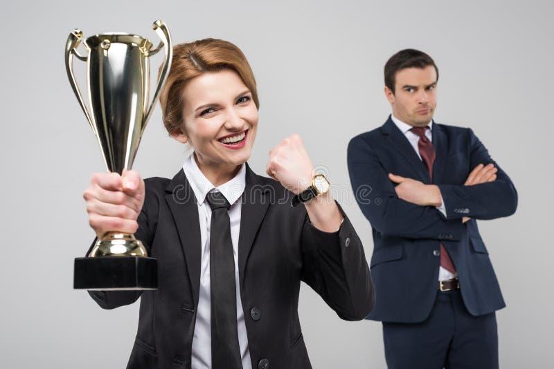 mulher de negócios entusiasmado com copo do troféu e homem de negócios da virada atrás, fotos de stock
