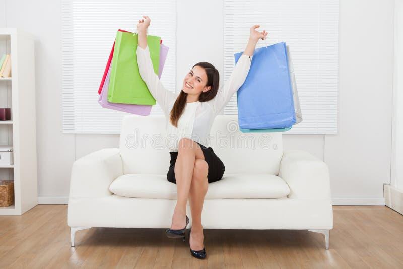Mulher de negócios entusiasmado que guarda sacos de compras no sofá imagens de stock