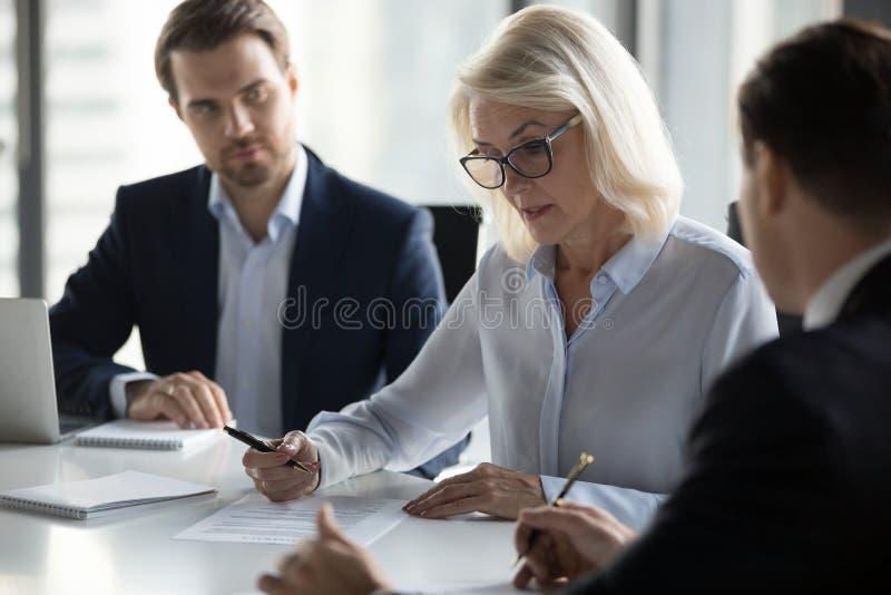 Mulher de negócios envelhecida concentrada que verifica o acordo antes do signin fotografia de stock royalty free