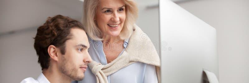 Mulher de negócios envelhecida do mentor que ajuda ao empregado novo com programa incorporado imagem de stock