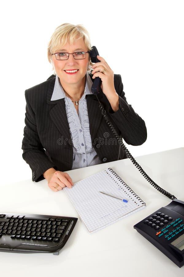 Mulher de negócios envelhecida média atrativa no escritório fotografia de stock royalty free