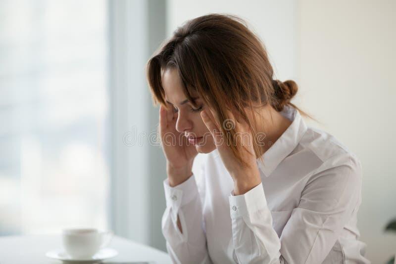 Mulher de negócios esgotada cansado que sente a dor de cabeça forte no trabalho a fotografia de stock
