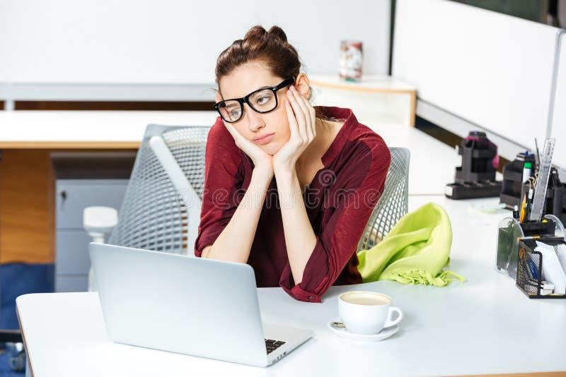 Mulher de negócios esgotada que trabalha com portátil e café bebendo no escritório fotos de stock