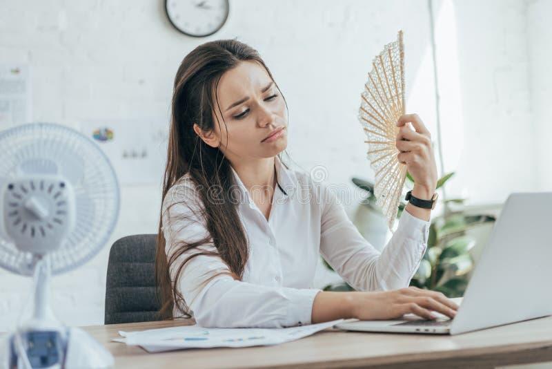 mulher de negócios esgotada que usa o portátil ao condicionar o ar com fã elétrico e fã da mão fotos de stock royalty free
