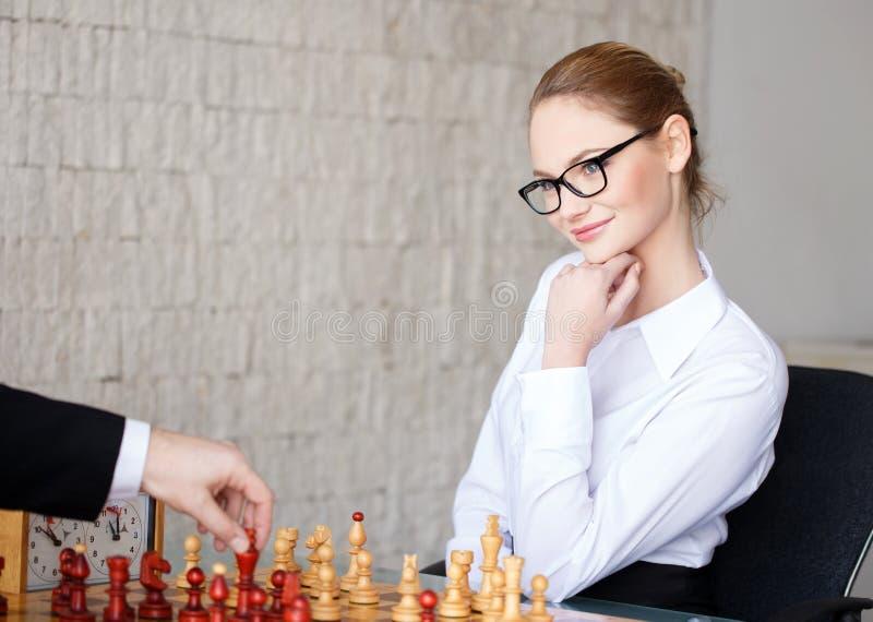 Mulher de negócios esperta segura que joga a xadrez e o sorriso fotos de stock