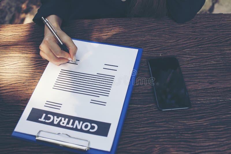 A mulher de negócios está assinando um contrato fotografia de stock
