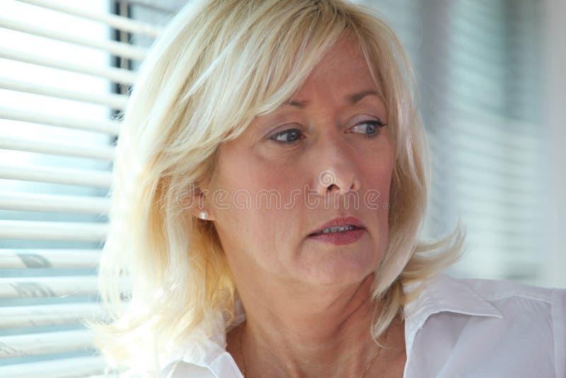 Mulher de negócios estada por cortinas de janela imagens de stock