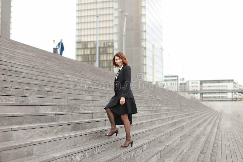 Mulher de negócios europeia que vai acima em escadas no fundo alto das construções foto de stock