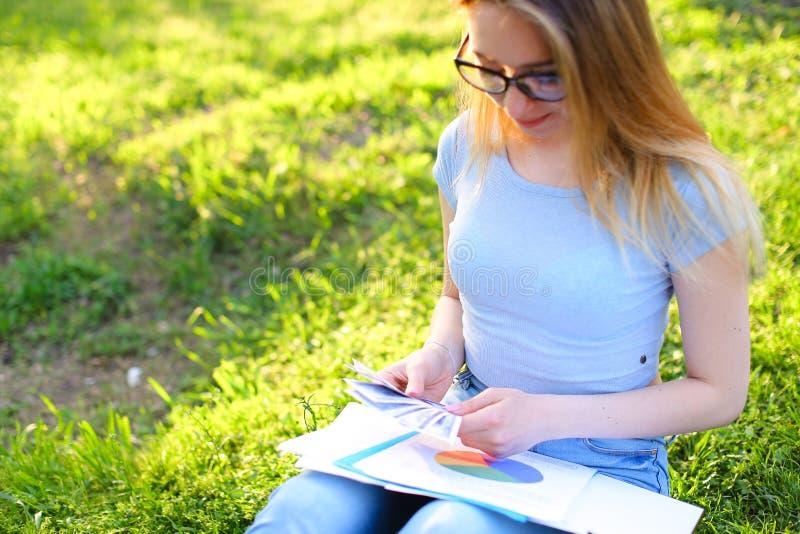 Mulher de negócios fêmea com os papéis que sentam-se na grama e que contam o dinheiro imagem de stock