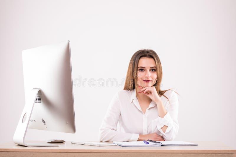 Mulher de negócios feliz bonita que usa o computador ao sentar-se na mesa no escritório no fundo branco fotografia de stock royalty free