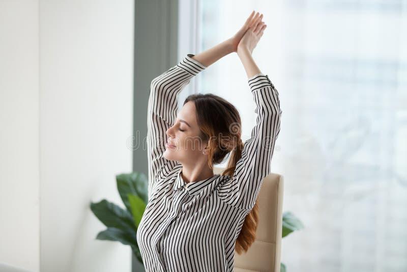 A mulher de negócios feliz calma relaxa no local de trabalho durante uma ruptura fotografia de stock