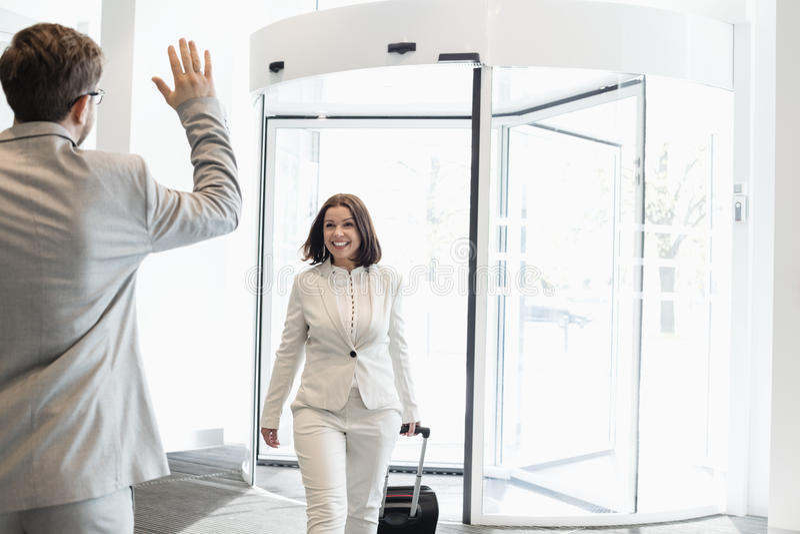 Mulher de negócios feliz com bagagem que anda para o colega masculino no centro de convenções imagem de stock royalty free