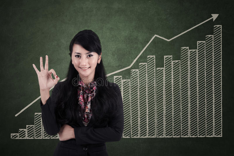 Mulher de negócios feliz com sinal aprovado na carta de barra do lucro fotos de stock