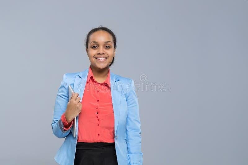 Mulher de negócios feliz do sorriso da menina afro-americano nova do tablet pc da posse da mulher de negócio imagens de stock