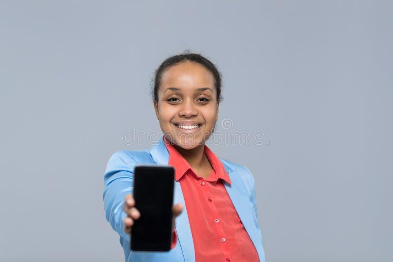 Mulher de negócios feliz do sorriso da menina afro-americano vazia esperta nova da tela do telefone da pilha da mostra da mulher  fotografia de stock
