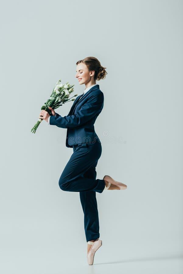mulher de negócios feliz em sapatas do terno e de bailado com o ramalhete das flores fotografia de stock