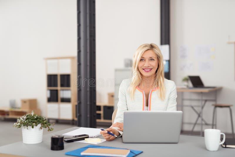 Mulher de negócios feliz em sua tabela com portátil fotos de stock royalty free