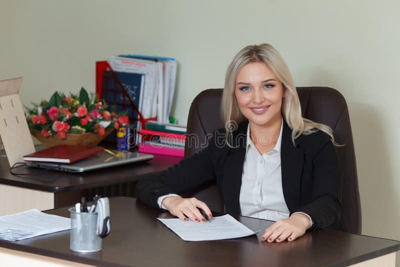 Mulher de negócios feliz no terno que sorri e que olha a câmera fotografia de stock royalty free