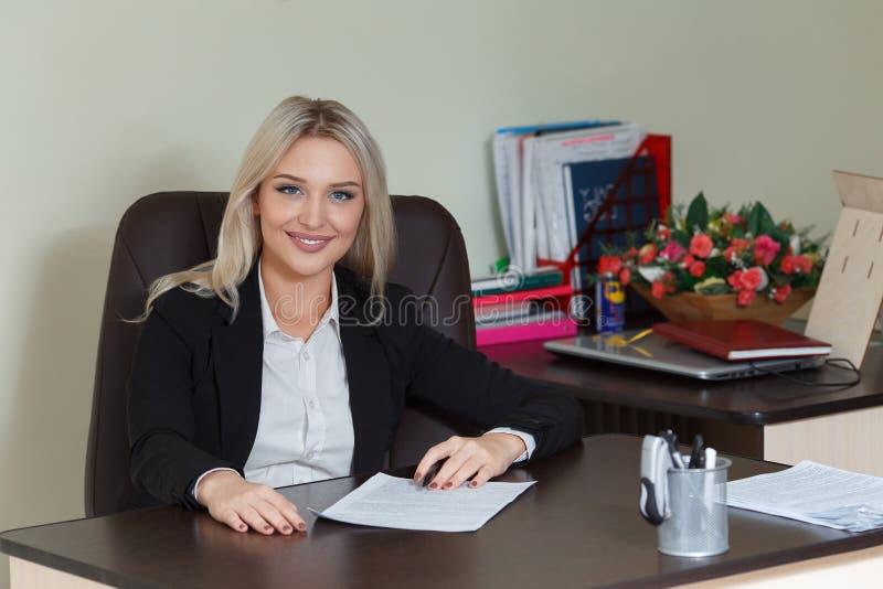 Mulher de negócios feliz no terno que sorri e que olha a câmera foto de stock