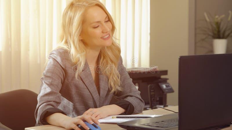 A mulher de negócios feliz no terno trabalha no computador no escritório foto de stock royalty free