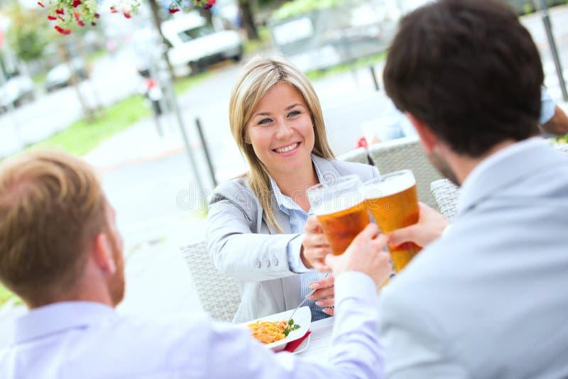 Mulher de negócios feliz que brinda o vidro de cerveja com os colegas masculinos no café do passeio fotografia de stock