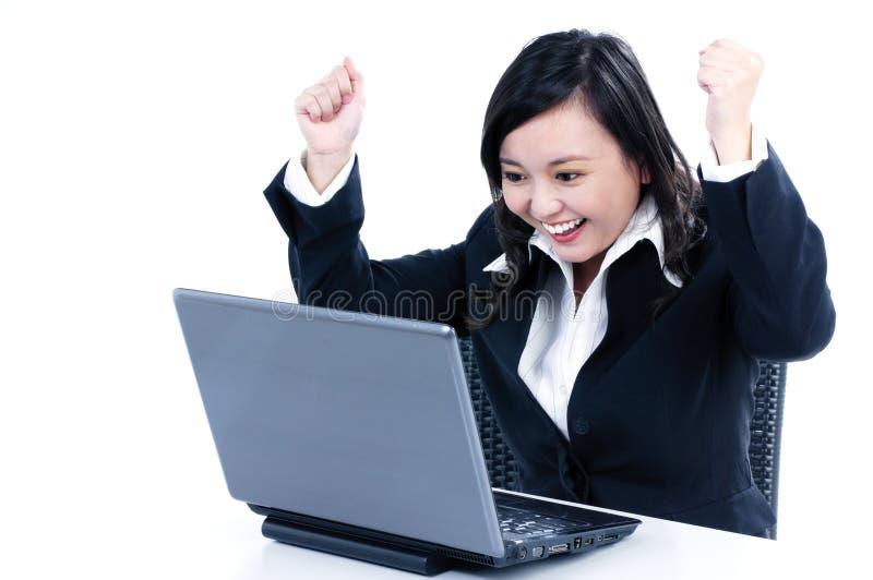 Mulher de negócios feliz que cheering na frente do portátil fotografia de stock royalty free