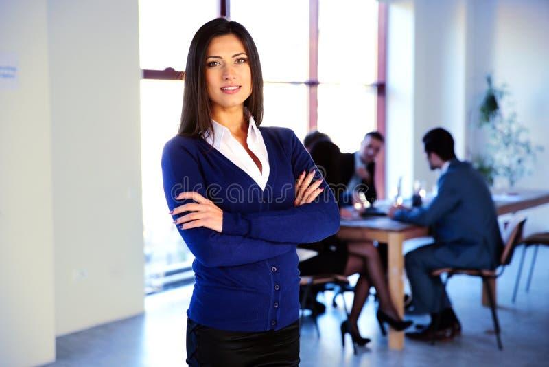 Mulher de negócios feliz que está com braços imagem de stock