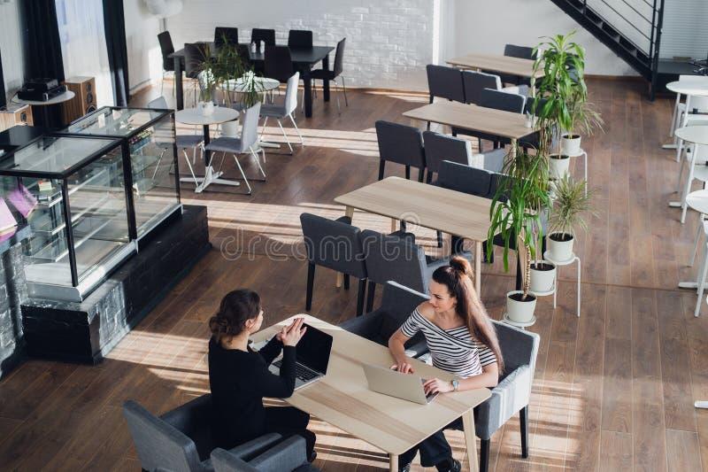 Mulher de negócios feliz que fala à mulher de negócios no escritório Duas mulheres que sentam-se na tabela com portáteis e trabal imagens de stock royalty free