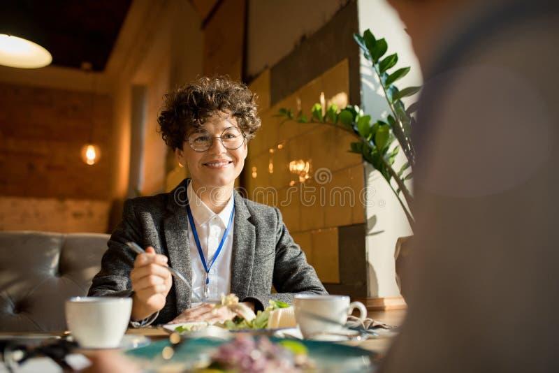 Mulher de negócios feliz que fala ao colega sobre o almoço fotografia de stock royalty free