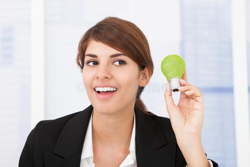 Mulher de negócios feliz que guarda a ampola verde foto de stock royalty free