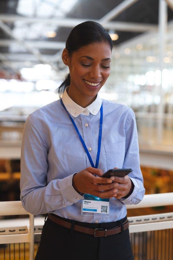 Mulher de negócios feliz que inclina-se em trilhos e que usa o telefone celular em um escritório moderno fotos de stock