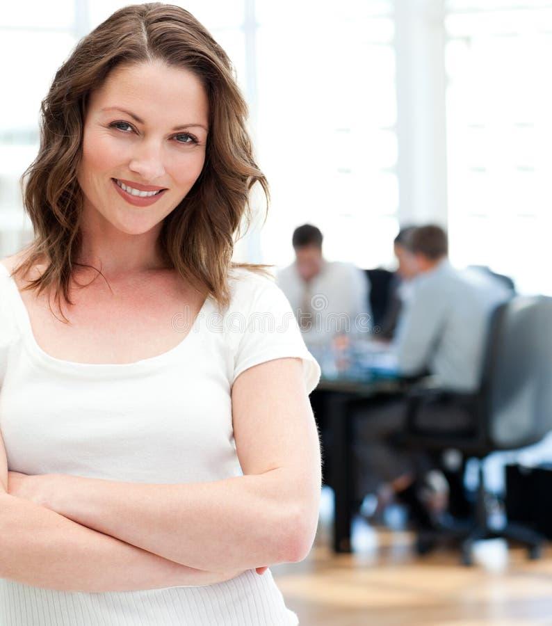 Mulher de negócios feliz que levanta na frente de sua equipe foto de stock royalty free