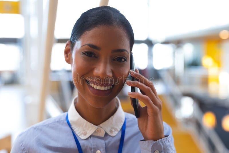 Mulher de negócios feliz que olha a câmera ao falar no telefone celular em um escritório moderno foto de stock royalty free