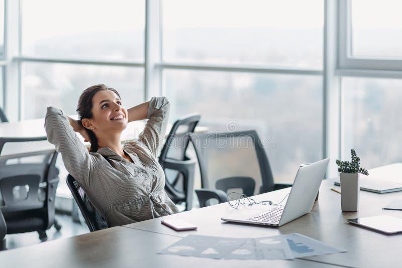 Mulher de negócios feliz que relaxa com mãos atrás da cabeça na mesa de escritório Conceito da fantasia foto de stock