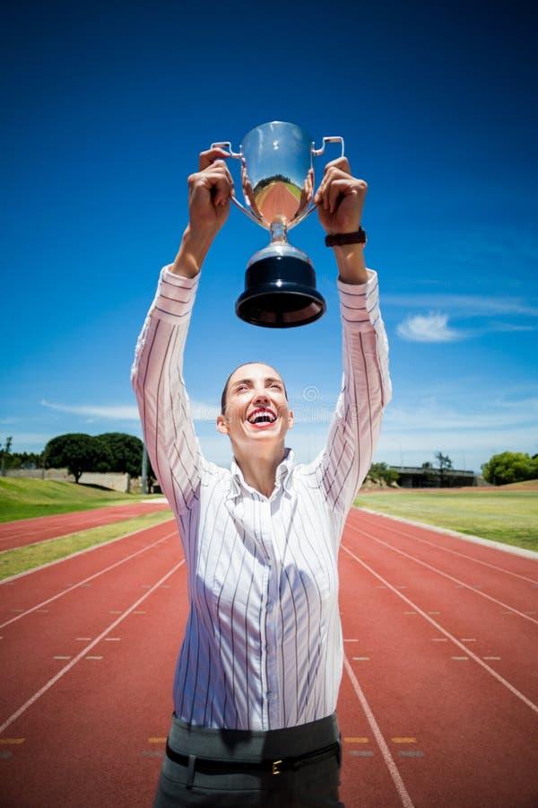 Mulher de negócios feliz que sustenta um troféu imagens de stock royalty free