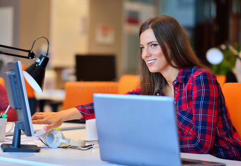 Mulher de negócios feliz que trabalha em seu portátil no escritório fotografia de stock royalty free
