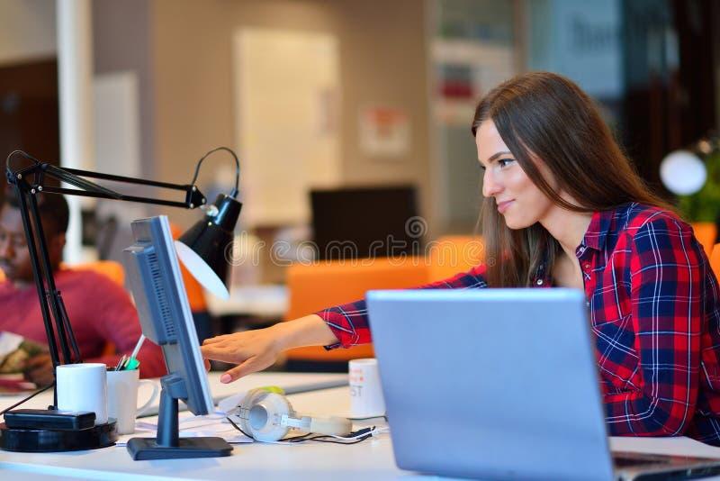 Mulher de negócios feliz que trabalha em seu portátil no escritório foto de stock royalty free