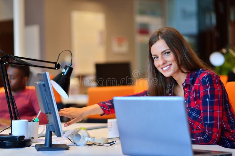 Mulher de negócios feliz que trabalha em seu portátil no escritório imagens de stock royalty free