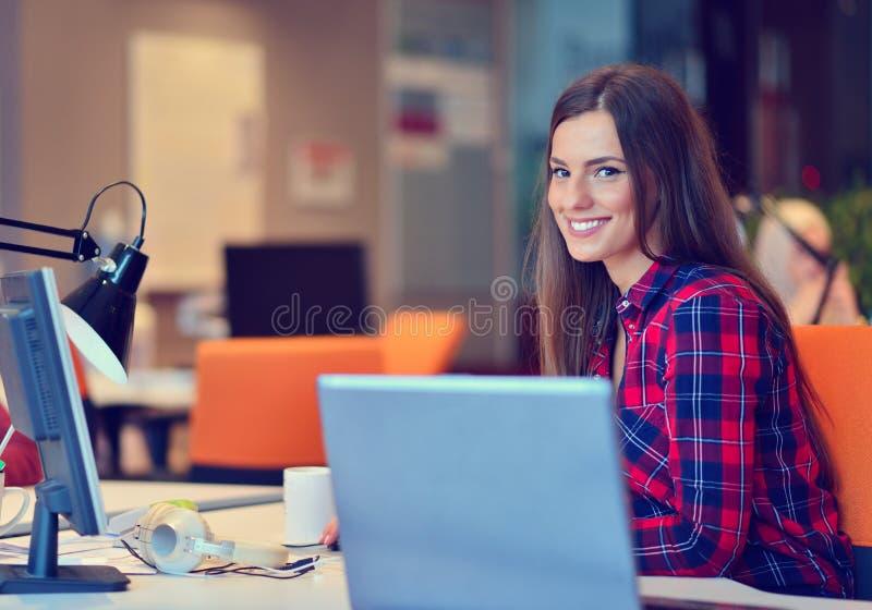 Mulher de negócios feliz que trabalha em seu portátil no escritório imagens de stock
