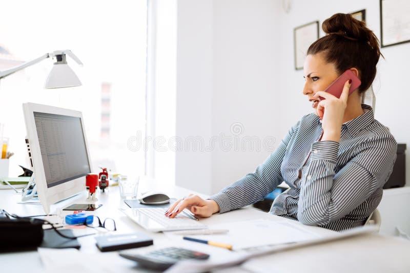 Mulher de negócios feliz que trabalha em sua mesa imagens de stock