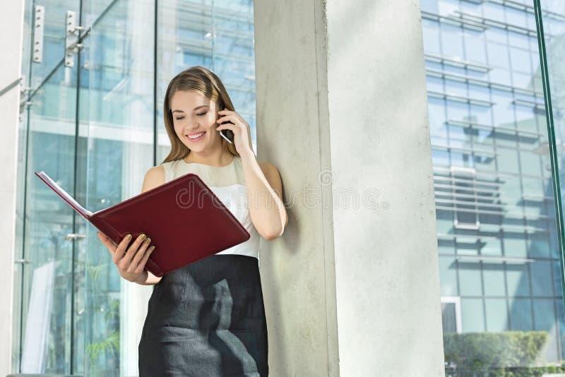 Mulher de negócios feliz que usa o telefone celular ao ler o arquivo no escritório imagem de stock royalty free