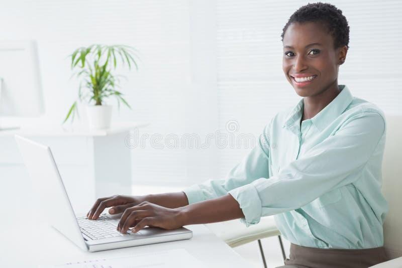 Mulher de negócios feliz que usa seu portátil imagens de stock royalty free