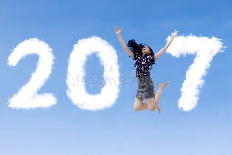 A mulher de negócios feliz salta com 2017 fotografia de stock